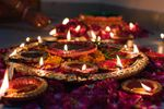Candles and colorful flowers laid out for Diwali